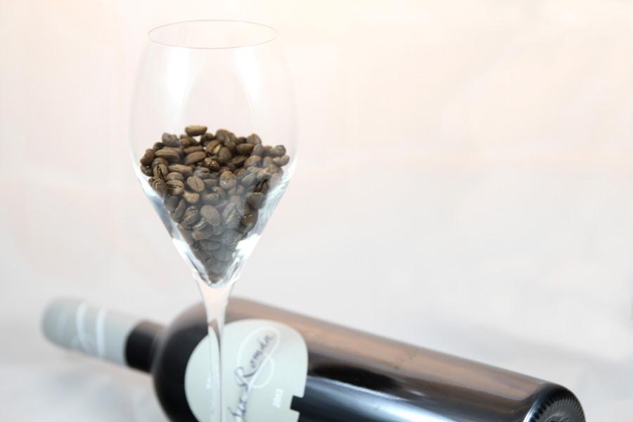 Flasa vína s pohárom. V pohári sú upražené kávové zrná.